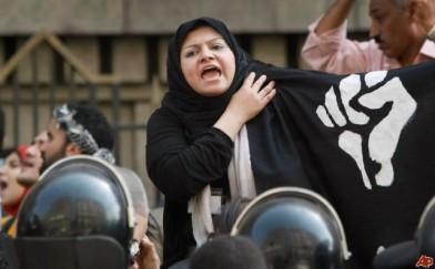"""Египетска жена държи знаме на соросоидният """"Отпор""""."""