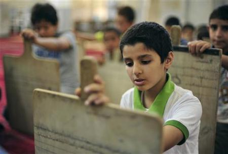 Libyan boys are seen with wooden slates as they memorize scriptures from the Koran at a school in Benghazi