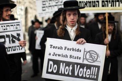 """На снимката младеж в Ерусалим държи лозунг, на който пише: """"Тората забранява Еврейскa държава. Не гласувайте!!!"""""""