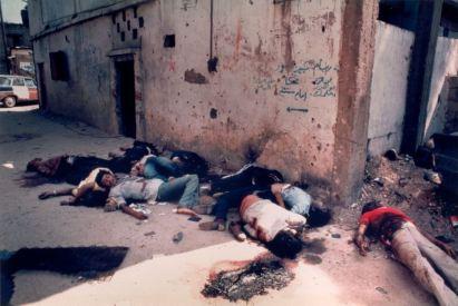 Тела на убити палестинци извън сградата на бежански лагери в Ливан, охранявани от израелски военни. Били са избити повече от 3500 палестинци. Клането започва на 16-ти септември 1982 г. и продължава 3 дни. (Снимка: Робин Мойър)
