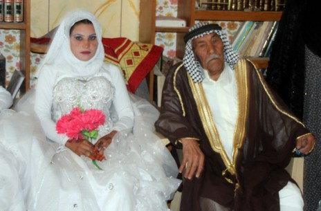 Musali Mohammed al-Mujamaie (R) a 92-year old Iraqi farmer sits next to Muna Mukhlif al-Juburi, his new 22-year old wife, during celebrations following their wedding in his home village of Gubban, just south of the central Iraqi city of Samarra on July 4, 2013. Mujamie got married with his two grandsons in a ceremony that carried on for four hours, with musical and dance performances and celebratory gunfire, and which was attended by local tribal and religious leaders. AFP PHOTO / STR