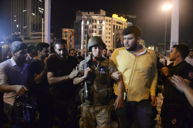 A Turkish soldier, arrested by civilians, is walked to be handed to police officers, in Istanbul's Taksim square, early Saturday, July 16, 2016. Members of Turkey's armed forces said they had taken control of the country, but Turkish officials said the coup attempt had been repelled early Saturday morning in a night of violence, according to state-run media. (AP Photo/Selcuk Samiloglu)