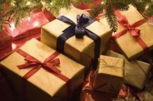 Christmas presents piled underneath a christmas tree.